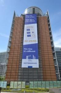 """Le bâtiment Berlaymont avec une affiche portant l'inscription : """"Cette fois-ci, c'est différent, votre voix compte"""" en néerlandais, français et anglais"""